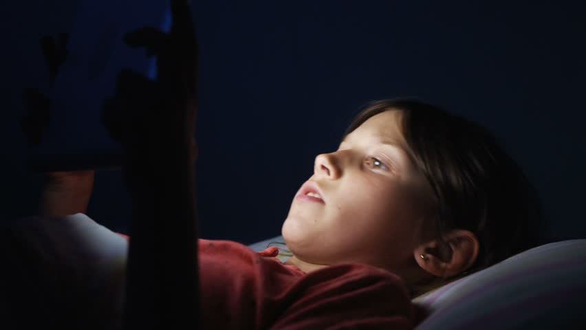 Caucasian girl lying in bed playing tablet in social internet in dark blue light under blacket. Childhood, communication and technology concept   Shutterstock HD Video #1011502577