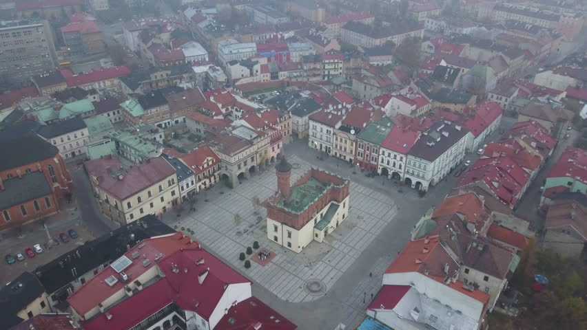 Foggy/Hazy Day in Tarnow Poland - 4k Drone Shot of Main Old Town Square and Colorful Red Roofed Buildings. Church sits in the Middle of Frame | Shutterstock HD Video #1011505607