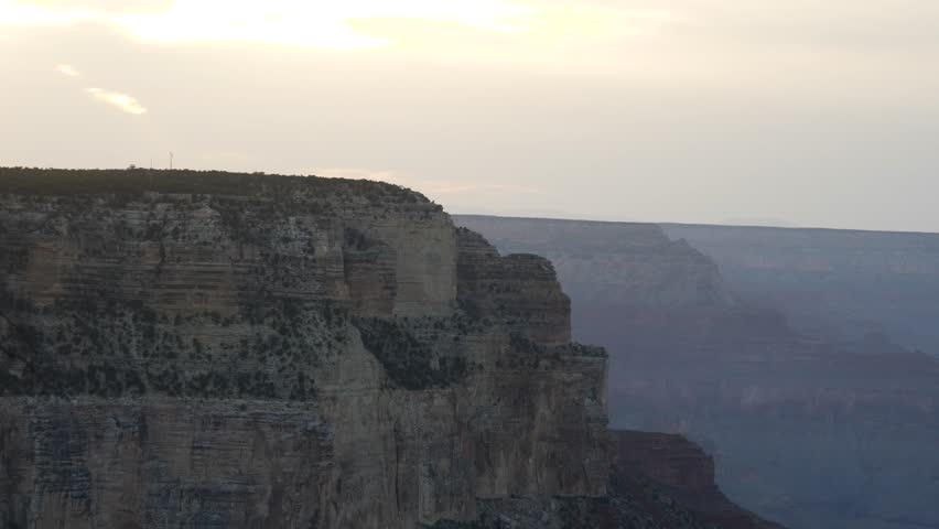 Rocky buttress with steep cliffs on the Southern rim of the Grand Canyon at dusk zooming out to a wide angle panorama