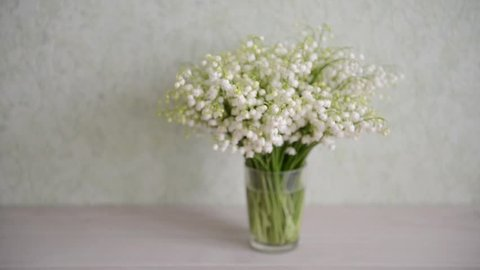 flowers lily of the valley stand on the table background