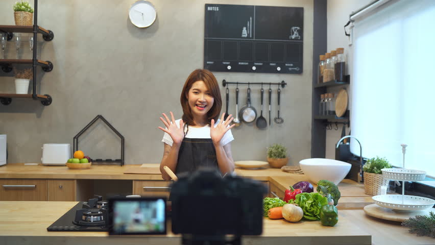 Young asian woman in kitchen recording video on camera. Smiling asian woman working on food blogger concept with fruits and vegetables in kitchen.