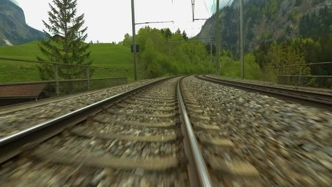 Locomotive moving up the tracks along a Swiss mountainside, traveling through a few tunnels. Shot in spring, with cloudy skies and green mountainside as background. Time- lapse footage