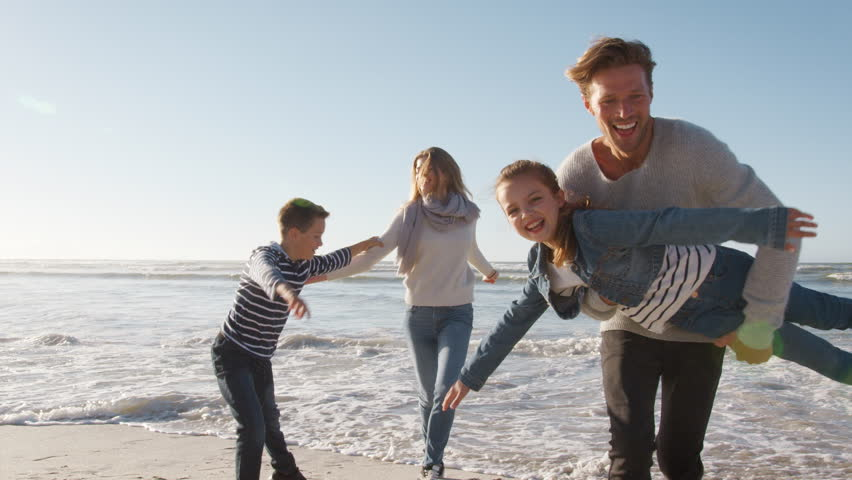 Family On Winter Beach Running Away From Advancing Waves