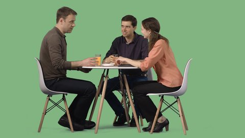 Two men and a girl sitting at a table in a cafe and talk