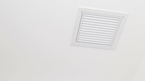 Man Replacing a Small Ceiling Air Filter Small dirty HVAC ceiling air filter removed and replaced with a clean air filter. Home air filter replacement of a small ceiling HVAC duct by a mature male.