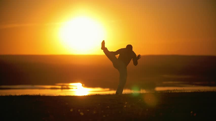 The fighter makes a handstand on the background of the setting sun, slow-motion #1011660797