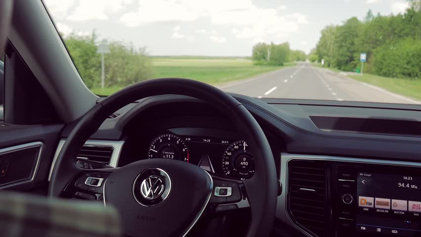 MINSK, BELARUS - MAY 28, 2018: A view on a steering wheel with driver's hands off it and on a road during driving Volkswagen SUV with adaptive cruise control on and lane keeping assist system on.  | Shutterstock HD Video #1011671567
