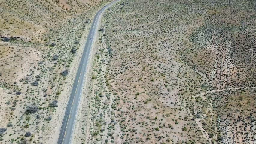 Desert mountain highway with white car outside Las Vegas Nevada USA | Shutterstock HD Video #1011693047