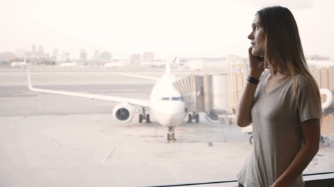 Young European woman talking on the phone near airport terminal window upset and frustrated after missing flight.