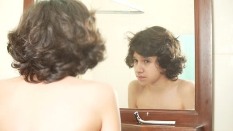 boy teenager is washing his face in front of a mirror. 4k.