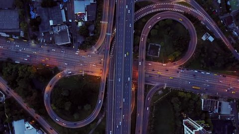 4K. Aerial view of infinity highway road interchange with busy urban traffic speeding on the road at night. Junction network of transportation in Bangkok, Thailand. taken by drone