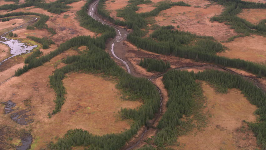 Anchorage, Alaska circa-2018. Aerial view of streams, grasslands and trees near Anchorage, Alaska. Shot from helicopter with Cineflex gimbal and RED Epic-W camera.