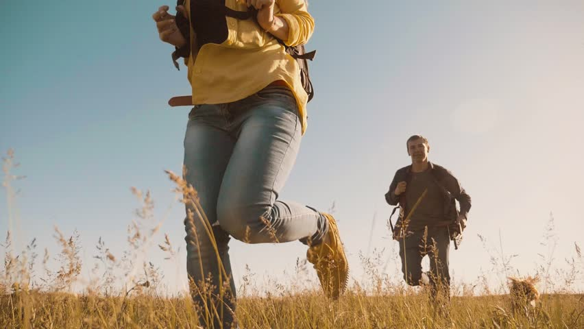 happy family are running slow motion video walking on nature boy run girl and mom in a field on trekking trip. tourists with a guitar backpacks traveling. happy family lifestyle run travel tourism