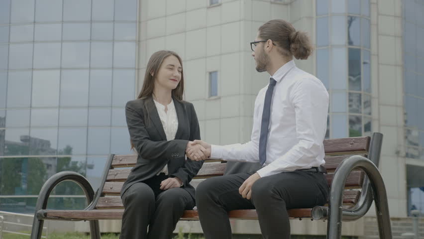 Young business people wearing formal suits smiling and making a pact by shaking hands on the bench in front the corporate building closing business deal