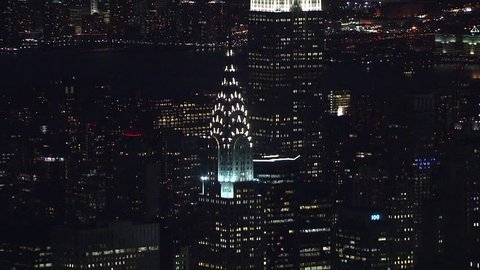 New York City, Circa 2018: Aerial NX establishing shot of Chrysler Building and Empire State Building lit up in lights at night