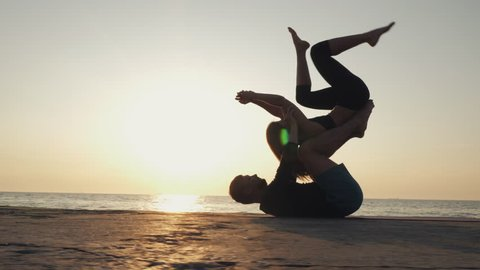 Acroyoga concept. Two sporty people practicing yoga in pair on nature sunrise background. Beautiful young couple doing stretching exercise on the sea beach. Slow motion