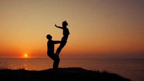 Amazing sillhouettes of beautiful couple doing acro-yoga on the sea or ocean beach at sunrise background, slow motion. Romantic scene. Healthy lifestyle, sport concept.