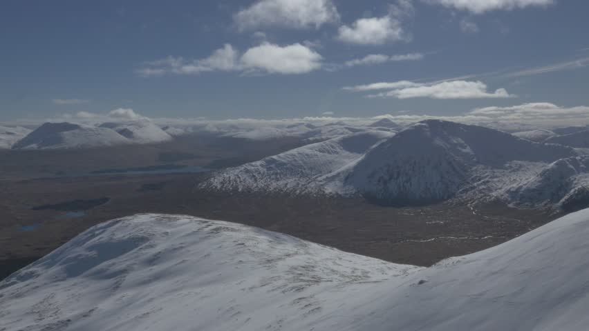 Aerial / Drone shot of Scottish Highlands, wide landscape of sky and mountains, moves to show closer mountain covered in snow, sunny blue skies, snowy highlands