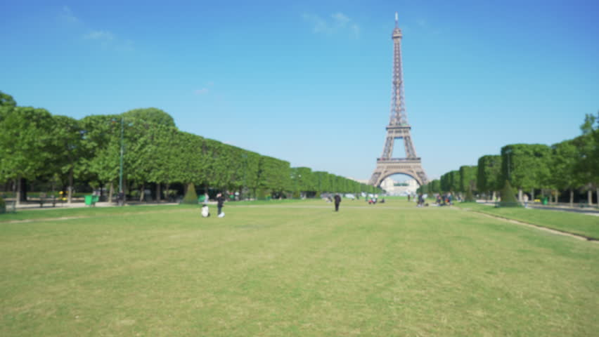 Defocused view of large flat grassy Field of Mars in Paris France. Wide shot of famous French landmark the Eiffel Tower
