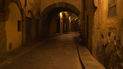 Low lighting archway street alley in Europe. Blurred background plate of arches on an empty street