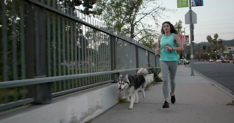 Millennial Female in Teal Running with Husky Dog with Smart Watch