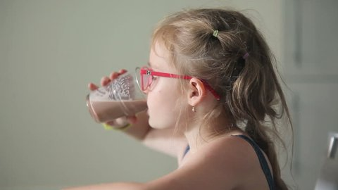 Blond girl drinks cacao from the glass