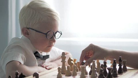 the blond boy is learning to play chess. He sits at the table and thinks over the course. The boy is wearing glasses, focused and attentive. Wants to checkmate