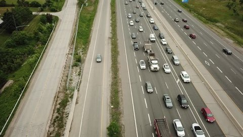 Top view aerial drone video of a massive eight lane highway.  Drone flies forwards while traffic moves underneath.