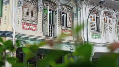 Singapore - May 2018: Traditional shophouses with plant in the foreground. Pedestal camera movement. Shallow depth of field. 4K resolution