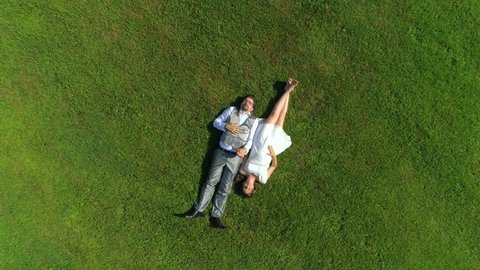 AERIAL TOP DOWN: Happy young couple laying in grass on summer day. Man and wife newlyweds relaxing in sunny park after wedding. Young man and pregnant woman lying and holding hands, expecting a baby
