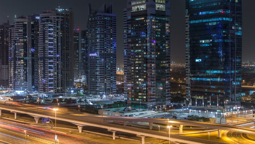 Aerial view of Jumeirah lakes towers with illuminated skyscrapers night timelapse with traffic on sheikh zayed road and metro line. Rooftop view from Dubai marina