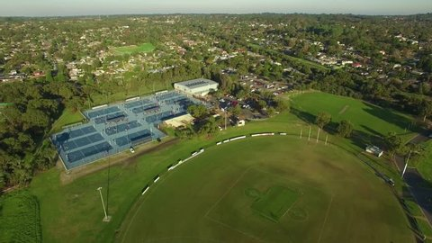 Slow aerial descend over sports oval and netball courts in Australia