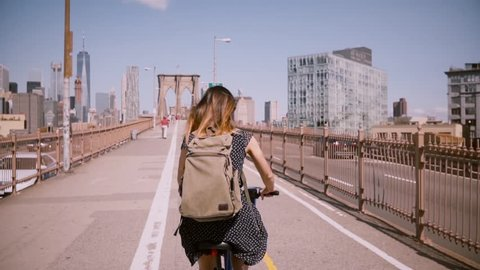 Back view woman with dark hair blowing in the wind riding a bicycle along a beautiful bike lane at Brooklyn Bridge, NYC.