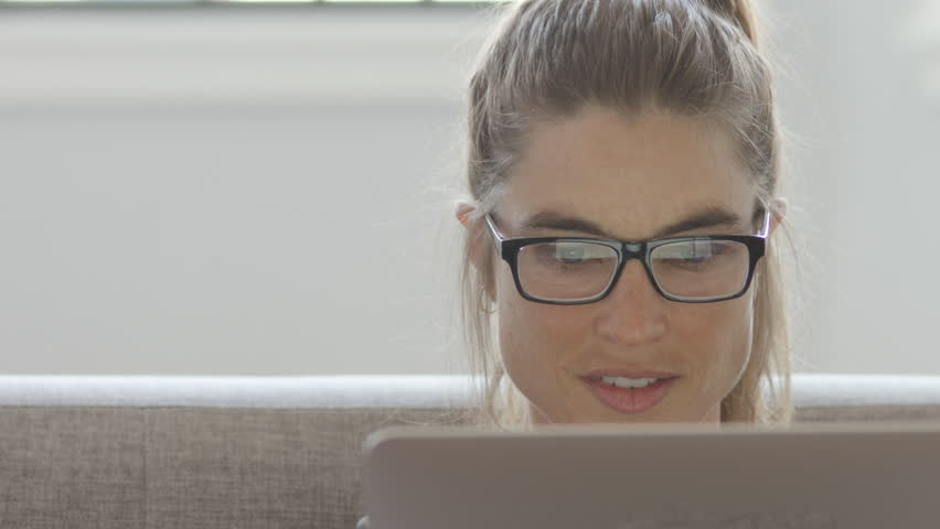 An attractive woman working on her computer on a couch, 4K slow motion | Shutterstock HD Video #1011898847