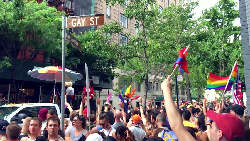 NEW YORK CITY - JUNE 25 2017: Spectators cheer floats from the LGBTQ Pride Parade passing Gay Street in Greenwich Village.