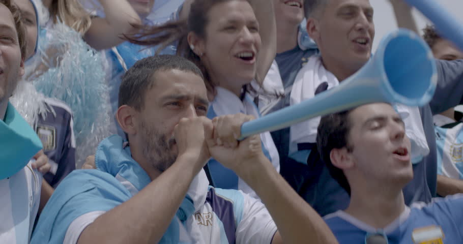 Argentinian football fans jumping and cheering at football match, slow motion