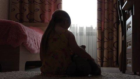Depressed little girl hugging teddy bear.