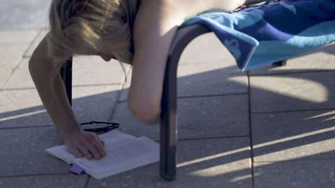 Closeup of a woman reading with her book on the ground at a swimming pool.