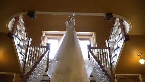 Wedding dress hanging from stairway.