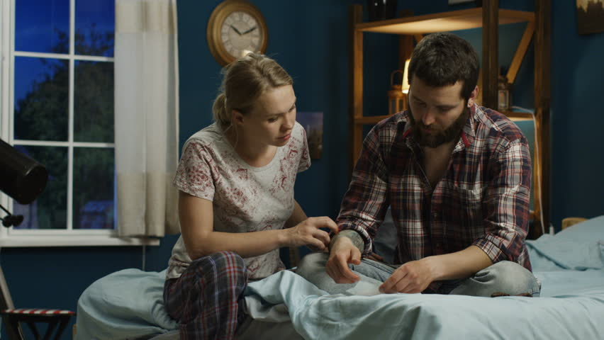 Young man and woman sitting on bed and computing sum for utility payments looking concerned because of money lack | Shutterstock HD Video #1011937277