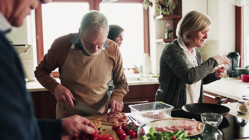 Senior couple cooking dinner together with friends at home. | Shutterstock HD Video #1011945497