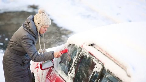 Young woman cleaning snow and ice off her car wind shield window