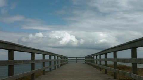 Horizon sky and sea over an empty pier on the cliff