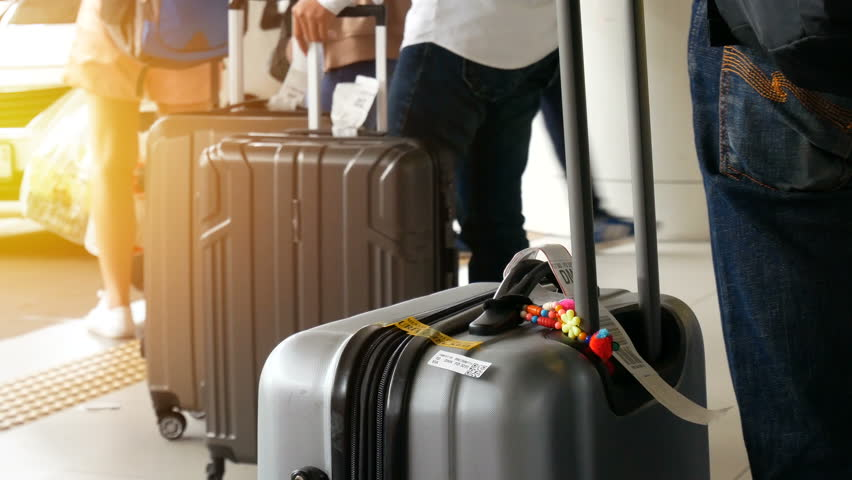 Passenger with big roller luggage standing on the line waiting for taxi queue at taxi parking lot at airport arrival terminal | Shutterstock HD Video #1011983027