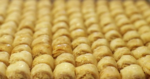 Baklava. CU rack focus on a tray of baklava, a rich sweet made of layers of filo pastry stuffed with chopped nuts and sweetened with syrup or honey.
