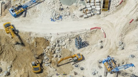 Large construction site including several excavators and cranes timelapse working on a building complex. Aerial top view from above at sunny day in Dubai, UAE
