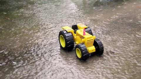 Children's toy car is placed on the road during the rainy season.