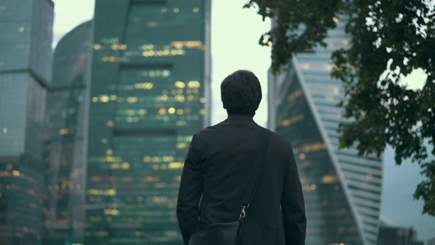 Rear view of a young unrecognizable businessman walking slowly and looking at skyscrapers in a summer evening. Moscow city background. Tracking medium shot | Shutterstock HD Video #1011991937
