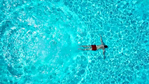 View from the top as a man jumping and dives into the pool and swims under the water