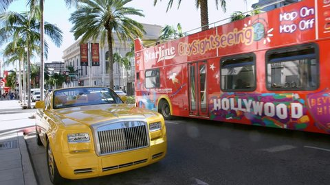 LOS ANGELES, CALIFORNIA, USA - JANUARY 8, 2015: Sightseeing tourist bus passing luxury Rolls-Royce luxury car and fashion boutique stores on Rodeo Drive in Beverly Hills, Los Angeles, California, 4K